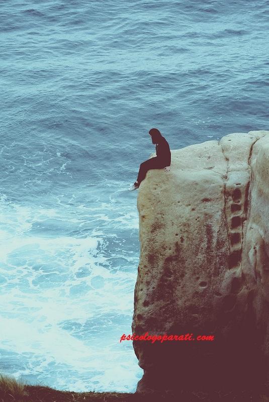 mujer que está al borde de un precipio vestida de negro, muy triste y con depresión