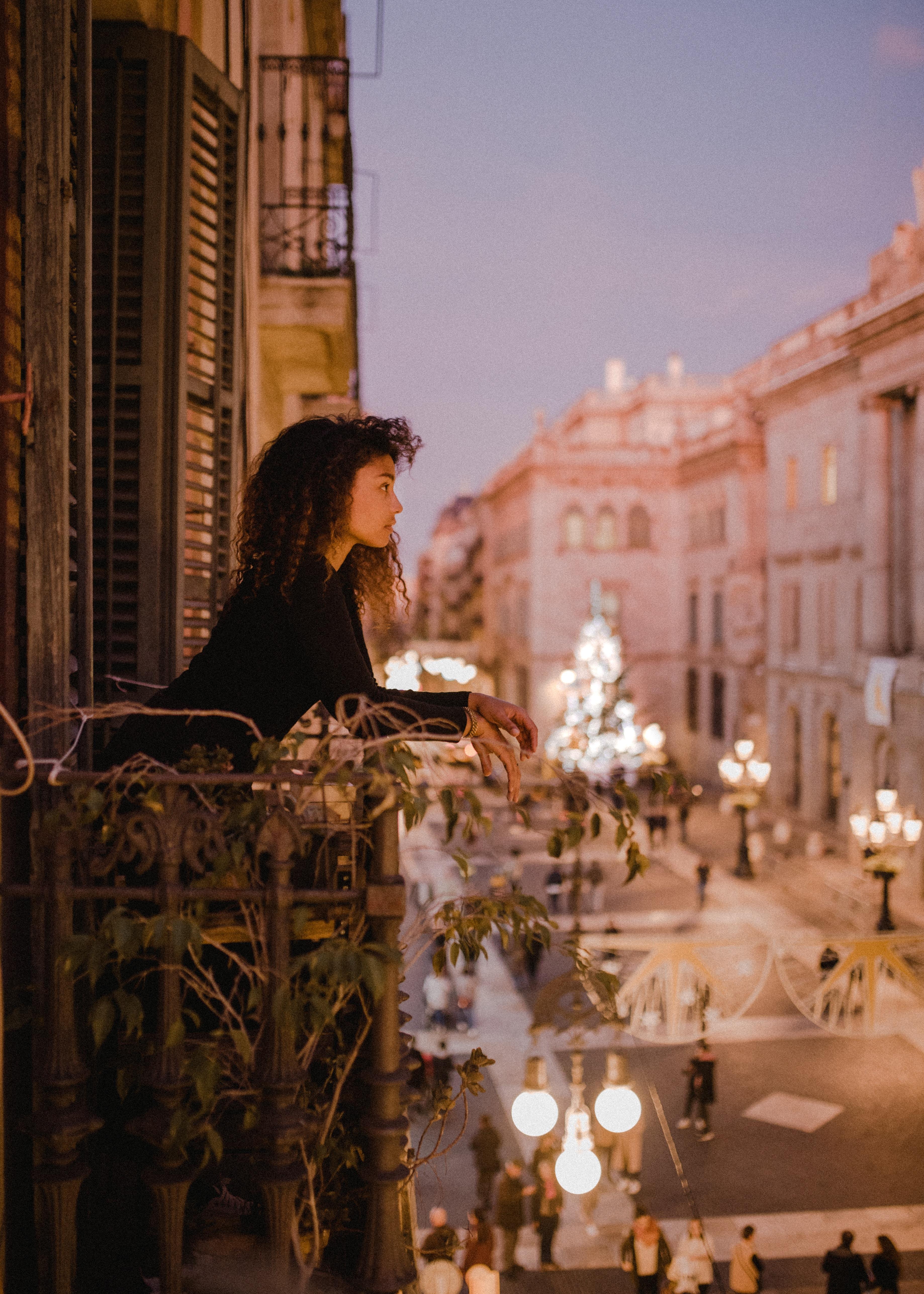 mujer en balcón de noche que está mirando hacia la nada, realizando un ejercicio de introspección