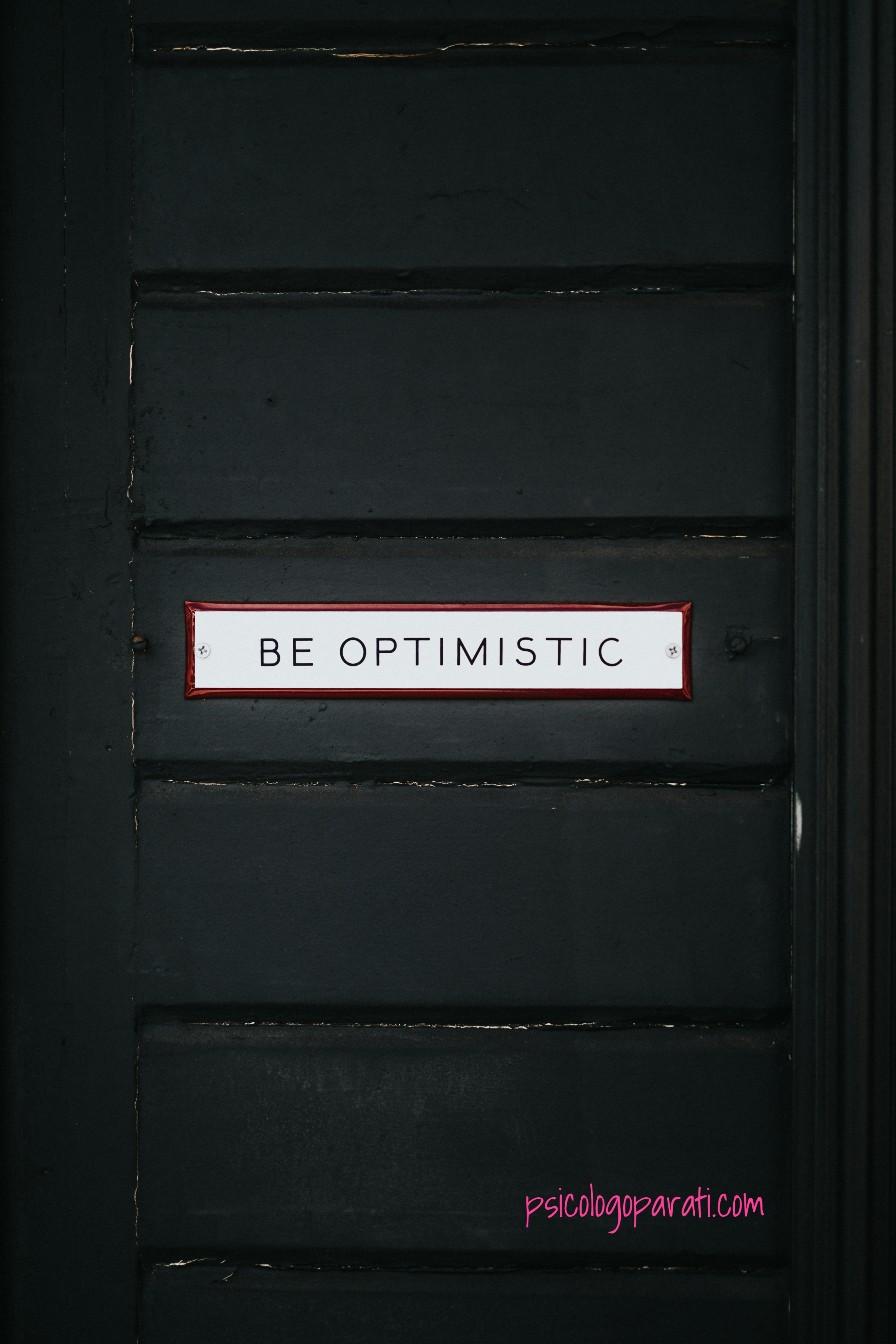 puerta negra con una frase de be optimistic para que se recalque el por qué hay que ser optimista cada día