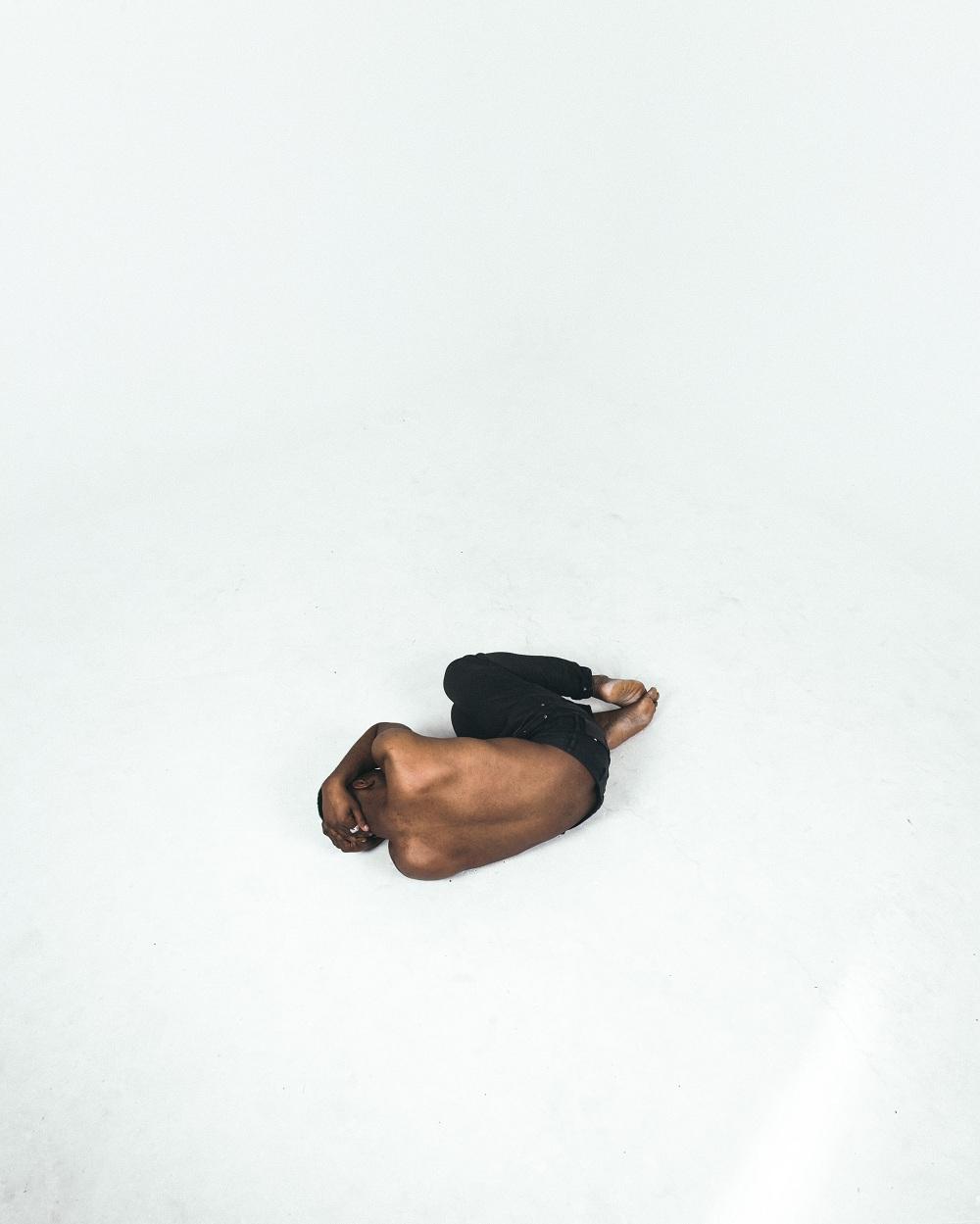 persona negra tumbada cogiéndose la cabeza con angustia porque tiene personalidad adictiva