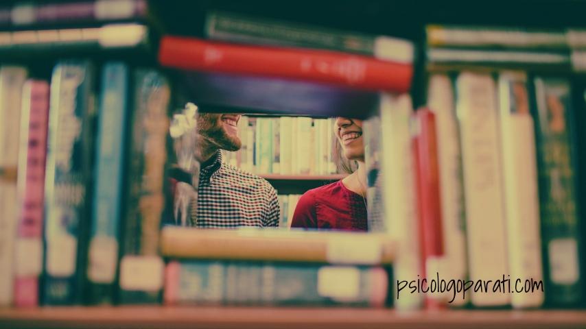 libros apilados con un agujero donde se ve una pareja sonriente que han terminado la relación y uno de ellos tiene que bloquear pensamientos obsesivos