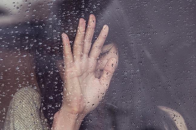 chica triste en cristal con gotas de lluvia, con la mano tapandose la cara, a punto de pedir cita de terapia online psicologica