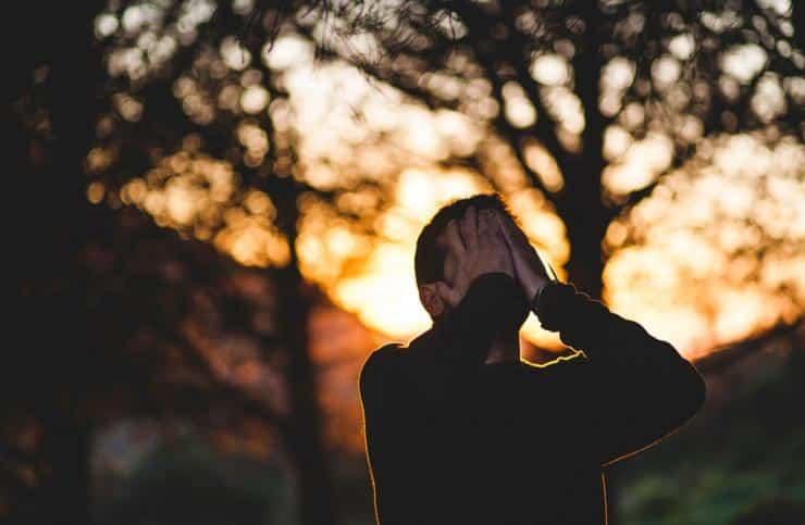 chico triste y abatido, con las manos en la cara en un bosque, que necesita terapia online psicologica