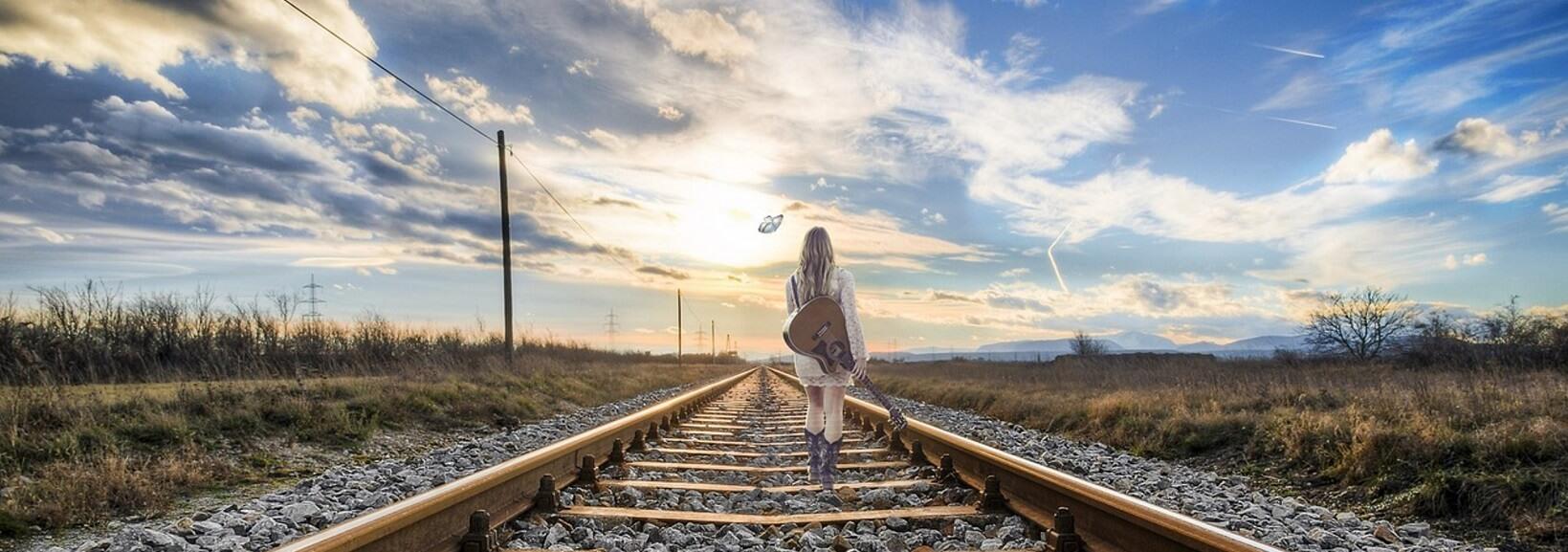 mujer caminando por vias de tren, mujer decidida a realizar psicoterapia por internet, porque es una mujer que necesita ayuda