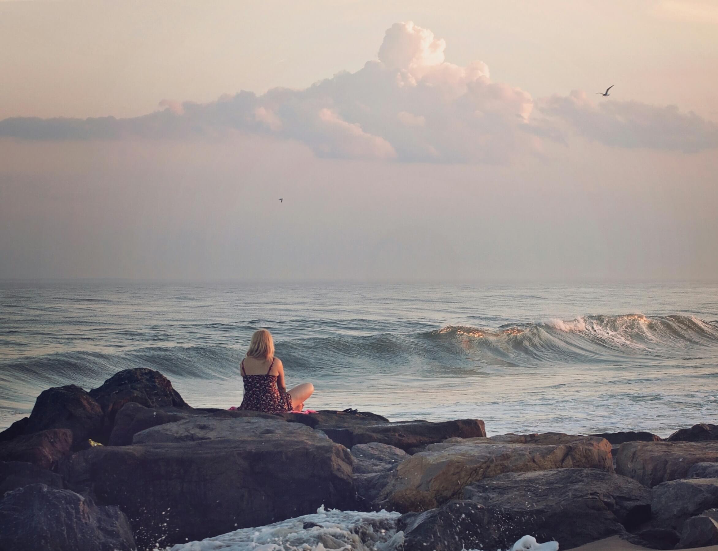 mujer rubia que está en las rocas frente al mar escribiendo un diario de agradecimientos