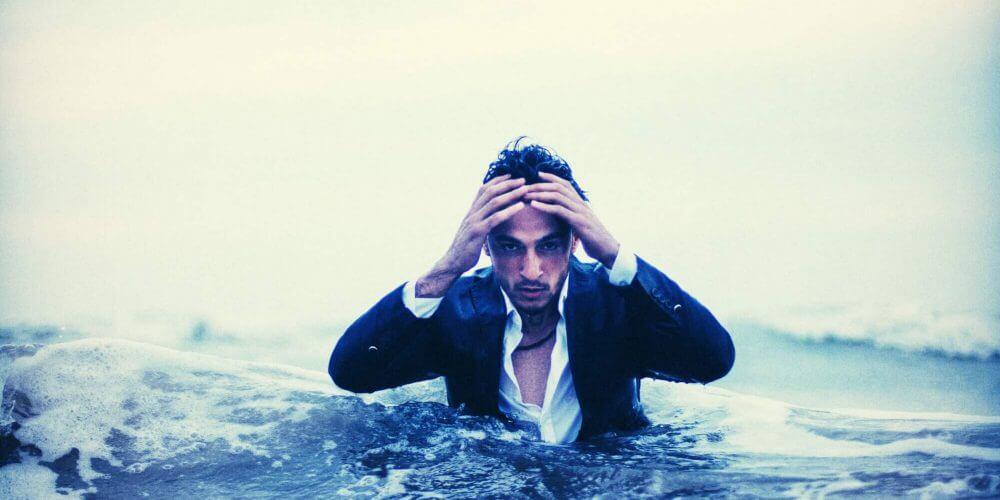 chico preocupado en traje dentro del agua, con las manos en la cabeza pensando en por qué estamos tristes o sufrimos de ansiedad