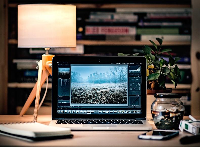 mesa de psicólogo online con portátil abierto y bloc de notas, lámpara encendida