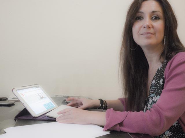 mujer psicoterapeuta mirando a camara mientras tiene un ordenador en las manos sobre una mensa