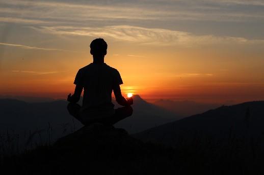 hombre que está en una puesta de sol y practica mindfulness y meditacion sentado con las manos sobre las rodillas