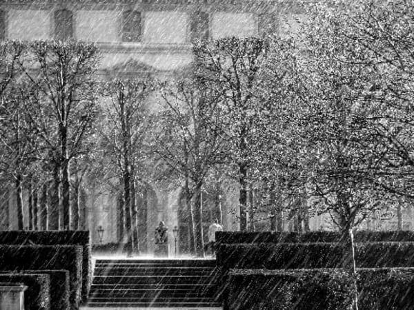 parque con árboles y de fondo un edificio cayendo lluvia y un chico sentado con capucha con pensamientos negativos