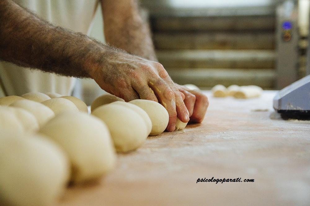 manos de hombre que tiene síndrome del impostor que están amasando una masa con harina