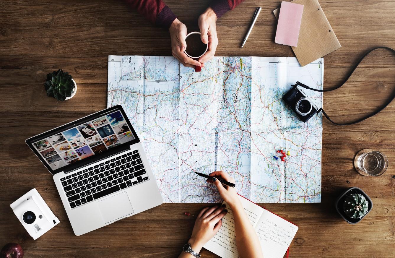 mapa sobre la mesa con brazos señalando el mapa, con cámara de fotos antigua y bolígrafos, es un mapa para identificar las propias emociones